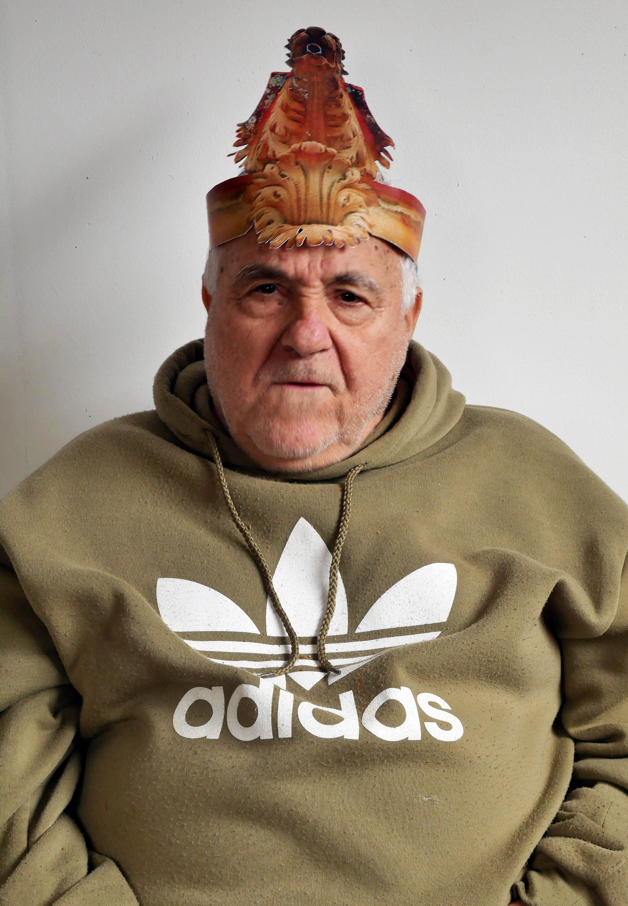A portrait of old man looking straight at the camera. He has a grumpy expression on his face. He is wearing a paper party hat in the form of a Gargoyle. He is wearing a beige sports jumper with a large white Adidas logo printed on the front.
